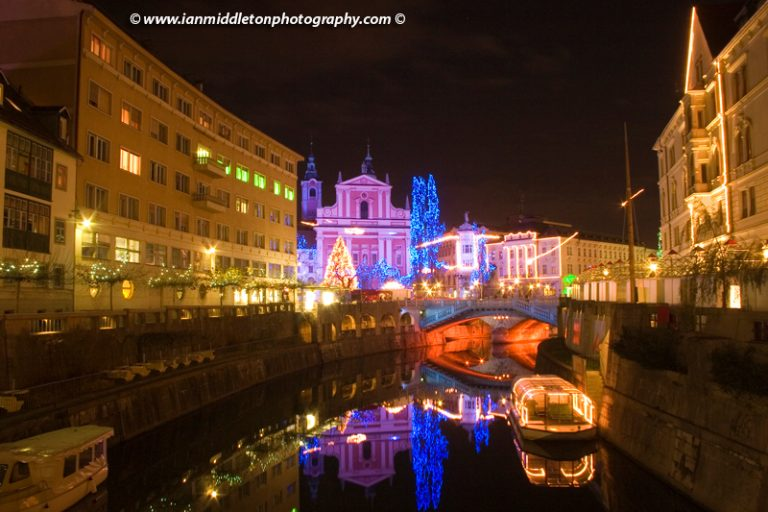 Christmas lights in Preseren Square in Ljubljana, reflected in the Ljubljanica River. Slovenia. The beautiful Franciscan church and christmas lights are beautiful sight every Christmas.