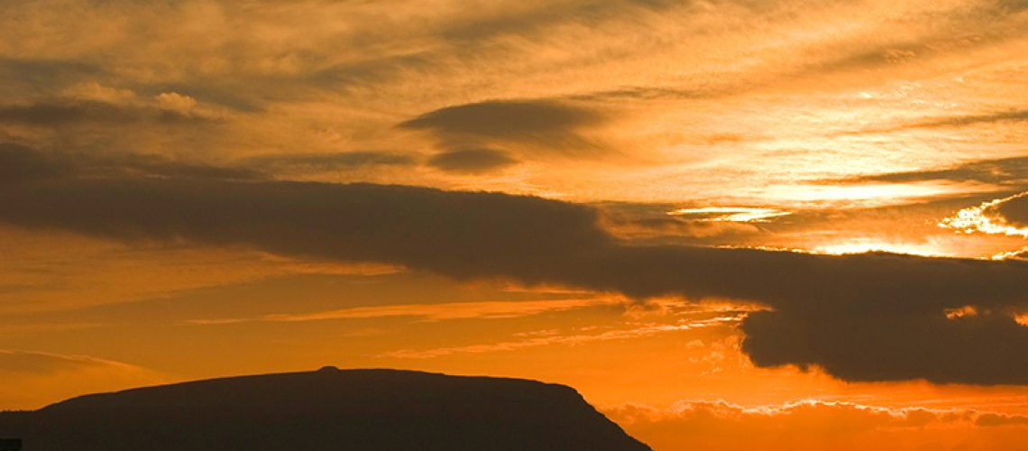 Sunset over Knocknarea Mountain and Sligo Bay, Ireland. The small mound on top of this mountain is the burial mound of Queen Maeve, the famous Queen who instigated the Táin Bó Cuailgne (Cattle Raid of Cooley). She is buried under a cairn of 40,000 tons of rock, which is 6000 years old. Legend says she is buried standing upright, spear in hand and facing Ulster, her enemy.